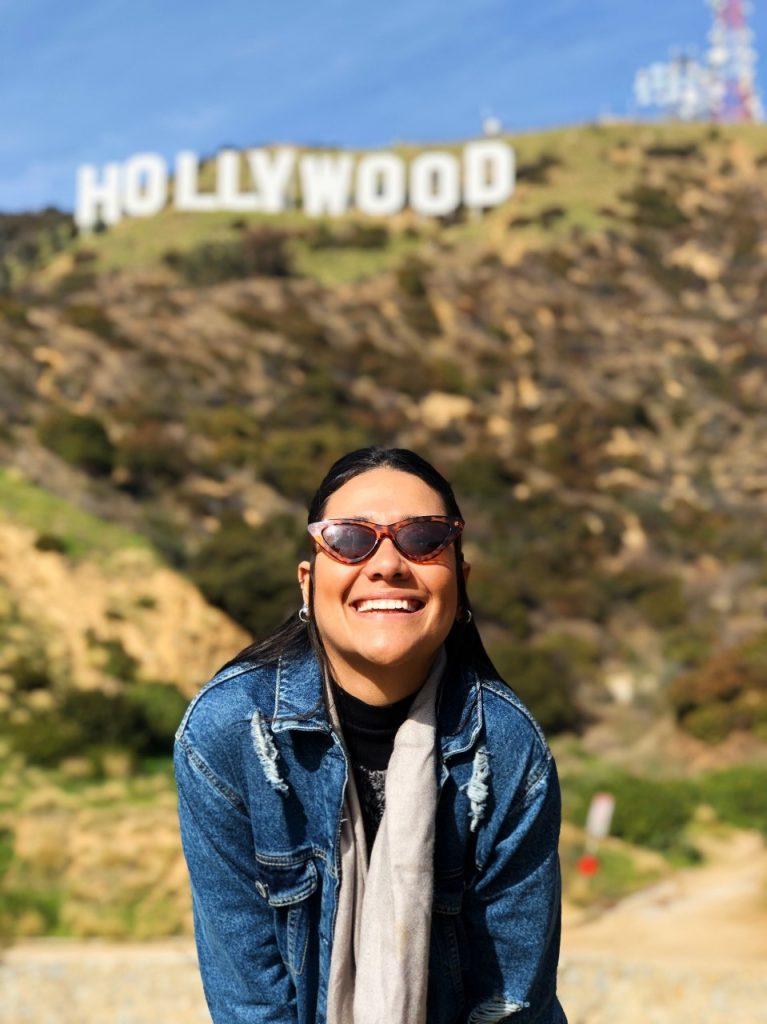 Ex-aluna da CSUN, Ysley Daltro, sorrindo em frente ao letreiro de Hollywood