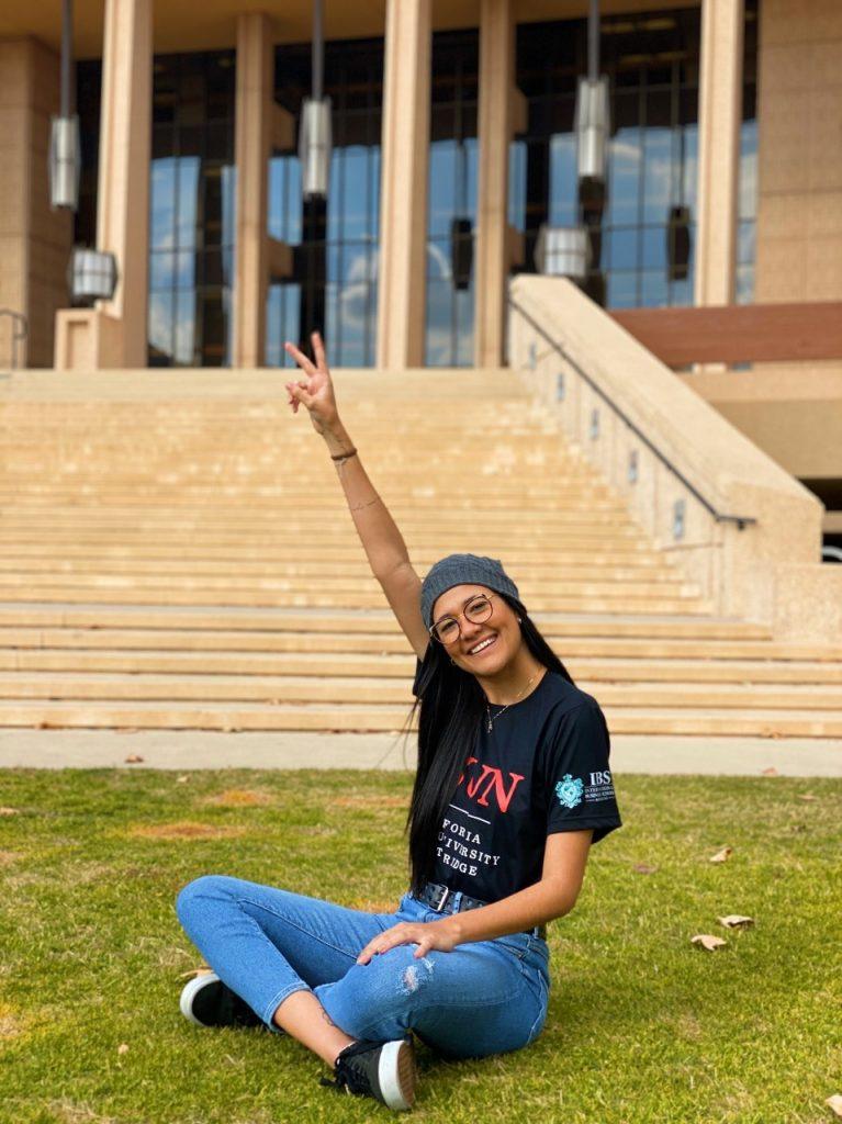 Aluna Ysley Daltro sentada em frente à escadaria da CSUN